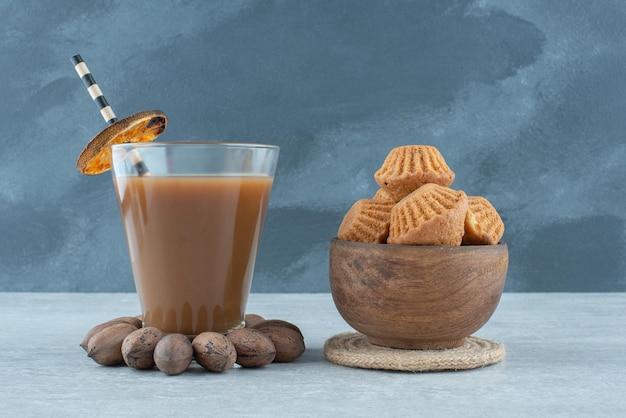 Un bicchiere di caffè con noci e biscotti
