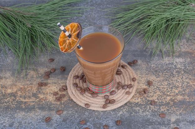 Bicchiere di caffè con paglia e fetta d'arancia. foto di alta qualità