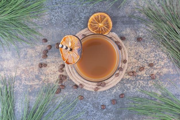Bicchiere di caffè con fette di paglia e arancia. foto di alta qualità