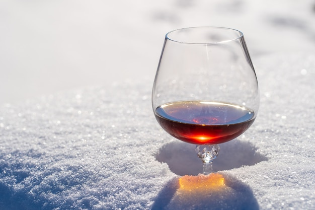Glass of cognac on a bed of snow and white background, close up. concept of christmas winter morning