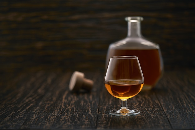 Glass of cognac on a black wooden table.