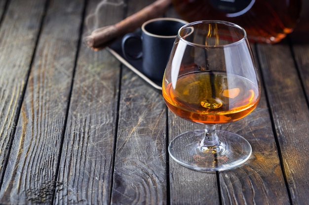 Glass of cognac or brandy with coffeeand smoking cigar on wooden table