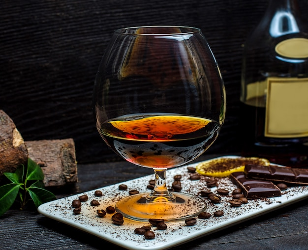 Glass of cognac and chocolate bars