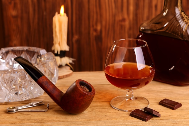 A glass of cognac, chocolate and smoking pipe on the oak table