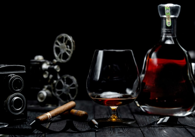Glass of cognac and cigar on a wooden table