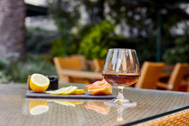 A glass of cognac, slices of lemon, a sandwich lie on the table on the restaurant's terrace