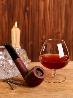 A glass of cognac and smoking pipe on the oak table