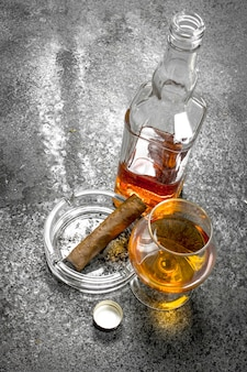 Glass of cognac with a cigar. on a rustic background.