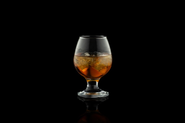 Glass of cognac with ice isolated on black.