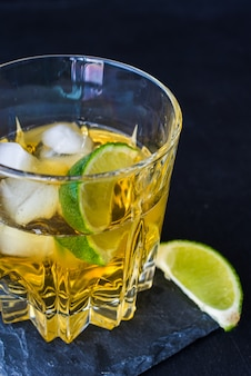 Glass of cognac with ice and lime on stone surface