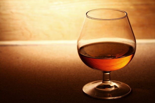 Glass of cognac over wooden surface
