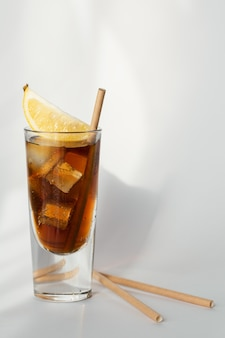 Glass of cola with ice, lemon and straw on a white wall