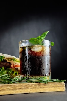 Glass of cola with ice, mint and rosemary on black background big sandwich, street food