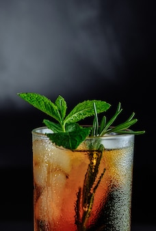 Glass of cola with ice, mint and rosemary