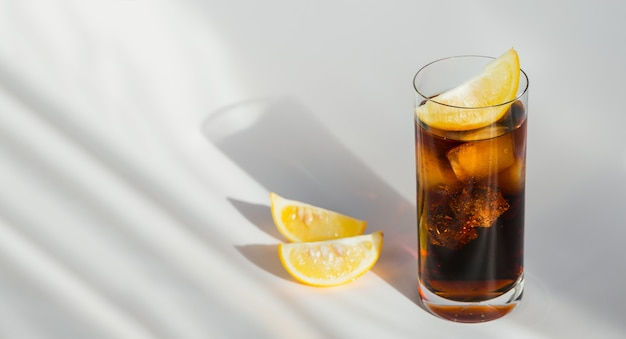 Glass of cola with ice and slices of lemon on a white background