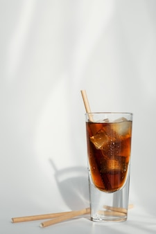 Glass of cola with ice and straw on a white wall