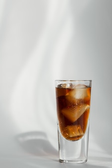 Glass of cola with ice on a white wall