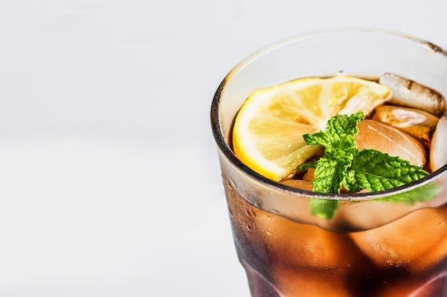 Glass of cola with lemon and aromatic leaves