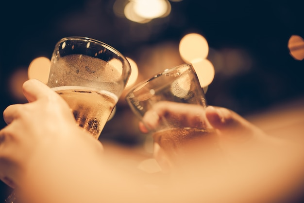 Glass of cold beer bottoms up with beautiful bokeh, friends drink beer together, dark tone