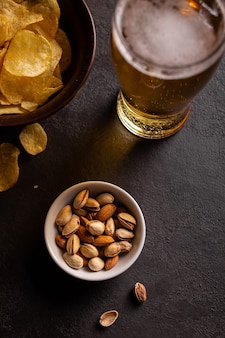 A glass of cold beer and pistachios