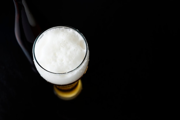 A glass of cold beer with foam and a bottle in the background black dark background with space