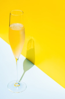 A glass of cold champagne with vapour that has shadow from sun light summer concept