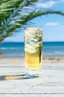 Glass of cold cidre or lemonade with ice on a seaside
