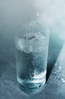 Glass of cold clear water on a blue background with falling drops into a glass.