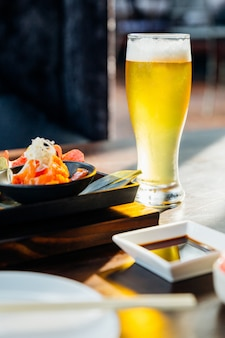 A glass of cold draft beer with froth on wooden table with blur meal in foreground
