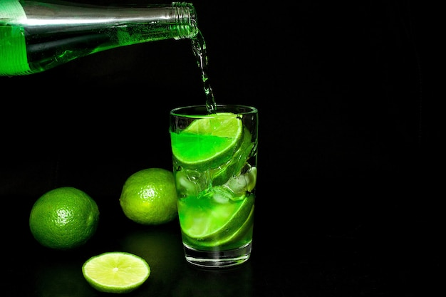 Glass of cold drink with ice and fresh ripe slice green limes on black