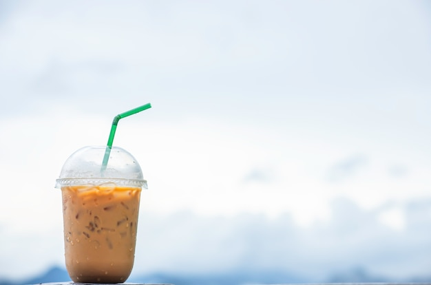 Glass of cold espresso coffee background blurry views sky.