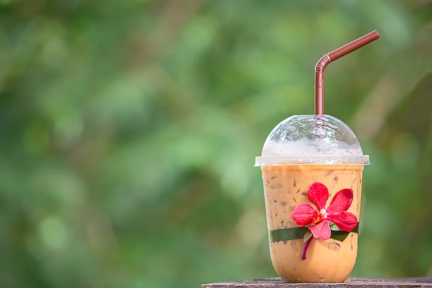 Glass of cold espresso coffee with red orchid flower on wooden table