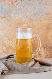 Bicchiere di birra dorata fredda isolato su una tovaglia leggera