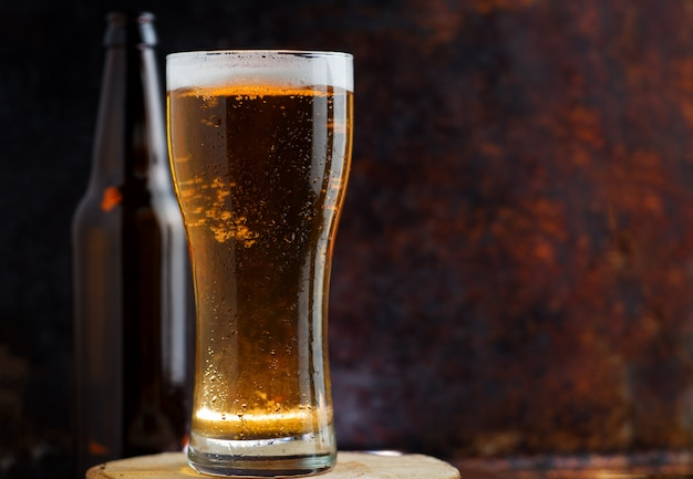 A glass of cold light beer on a dark rusty metal background copy space