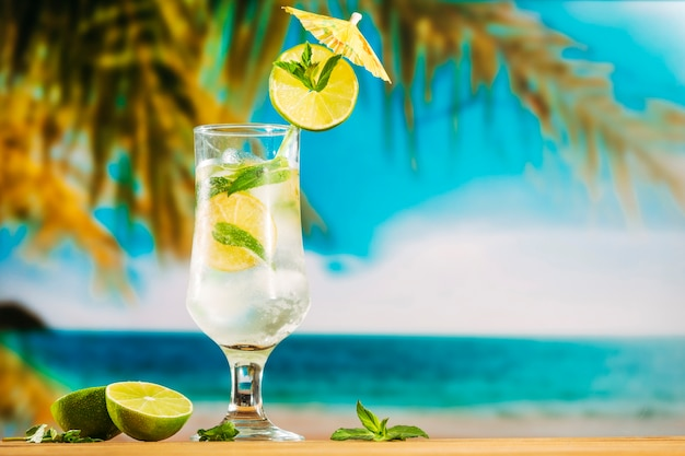 Glass of cold lime water with umbrella