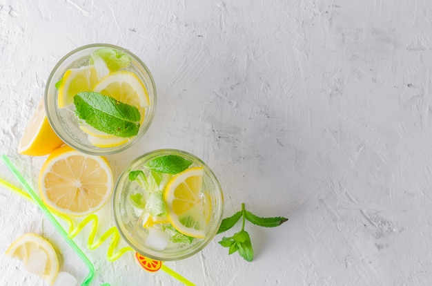 Glass of a cold mojito, juicy slised lemon and mint