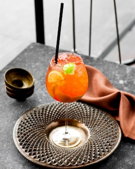 A glass of cold orange cocktail served in beautiful bronze plate