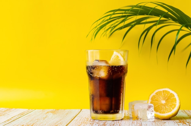 A glass of cold soft drink with lemon on wooden floor with coconut leaf and yellow background. summer drink concept.