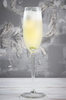 Glass of a cold sparkling wine cocktail drink with olive, on grey background.