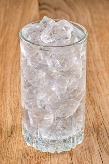 Glass of cold water with ice on wooden table
