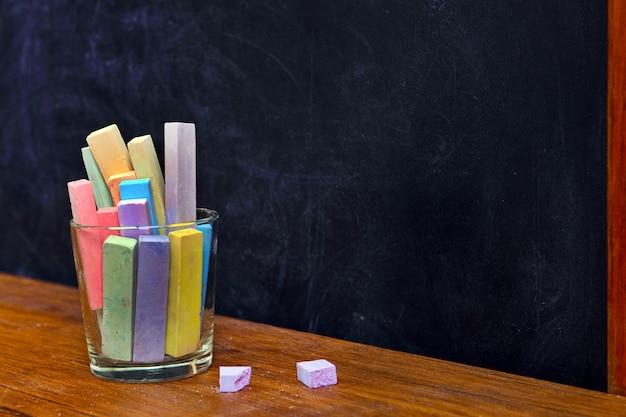 Glass of coloured chalk on desk in front of blackboard