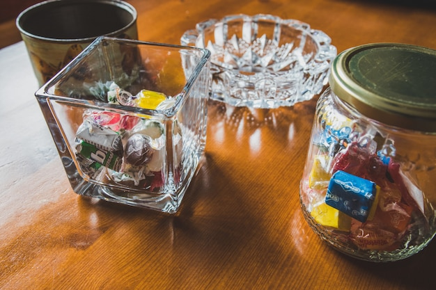 Glass containers filled with candies on wooden table