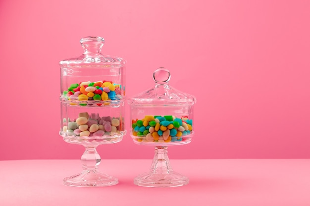 Glass containers with candies against pink background