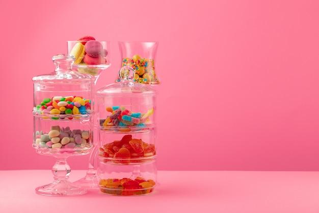 ピンクの背景にキャンディーとお菓子のガラス容器