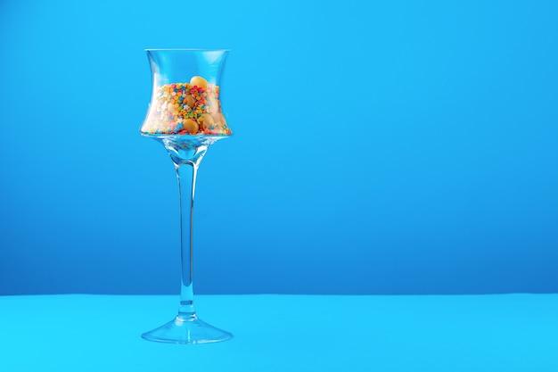 青い背景にカラフルなキャンディーとガラス容器をクローズアップ