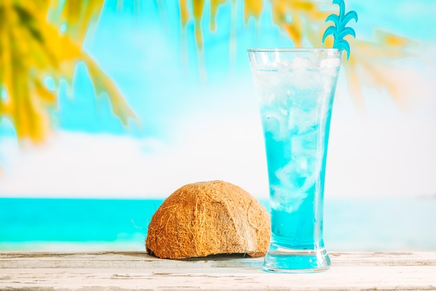 Glass of cooling blue drink and inverted coconut shell