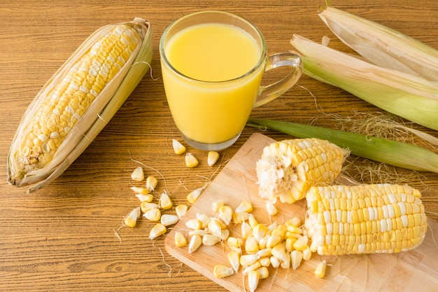 A glass of corn milk and fresh sweet corn on wooden table.