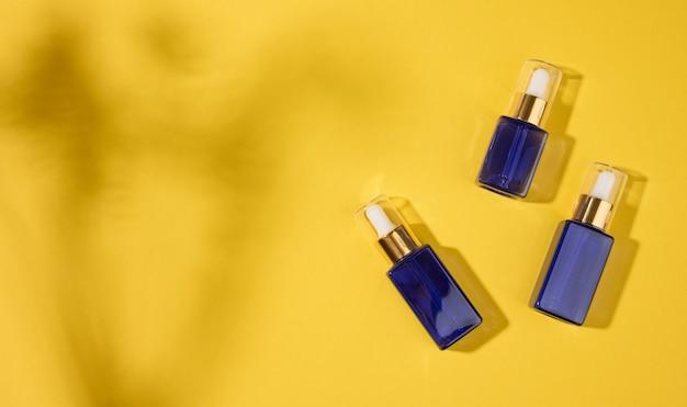 노란색 배경에 피펫이 있는 유리 화장품 파란색 병. 화장품 spa 브랜딩 모형, 평면도, 복사 공간