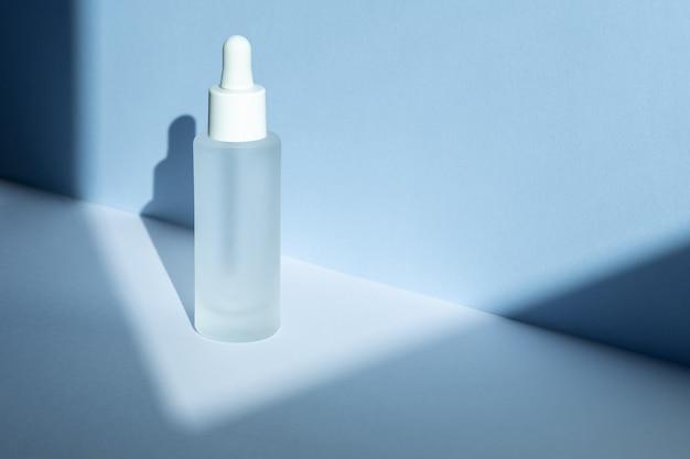 青い壁に幾何学的な影が付いたピペット製品パッケージのガラス化粧品ボトル、コラーゲンとペプチドを含む老化防止血清、化粧品、スキンケアのコンセプト。ハイアングルビュー