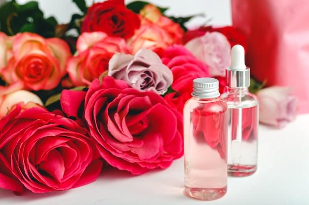 Стеклянные косметические бутылки сывороточного масла с цветочным фоном. цветочные розы натуральный органический косметический продукт